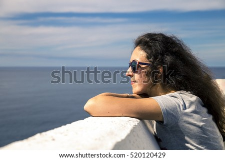 Young woman is enjoying the sunny day on the seaside of Norway
