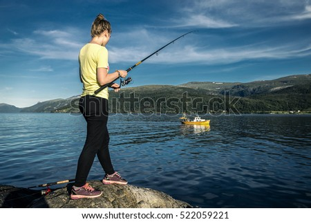 Young woman is fishing in Norway