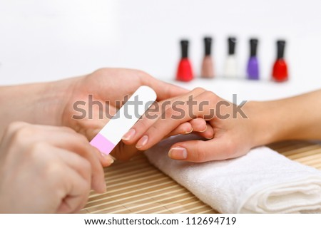 Young woman is getting manicure in a beauty salon - stock photo