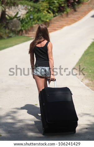 Young woman is going on the road and holding a suitcase with clothes - stock photo