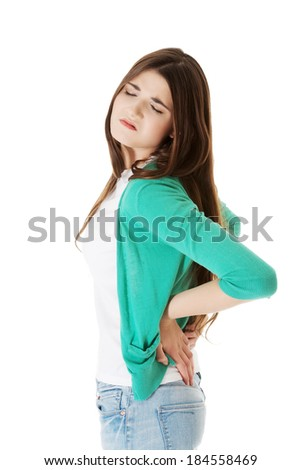 Young woman is having back pain. Isolated on white.