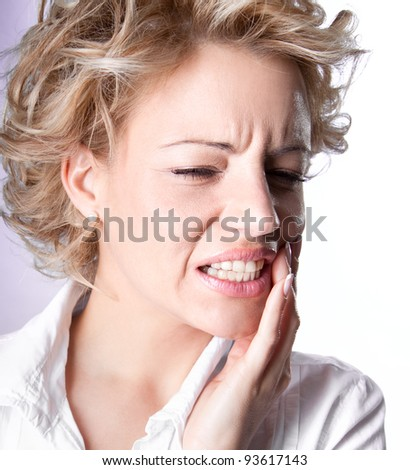 Young woman is having toothache isolated on white - stock photo