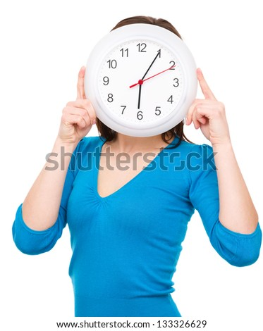Young woman is hiding behind big clock, isolated over white