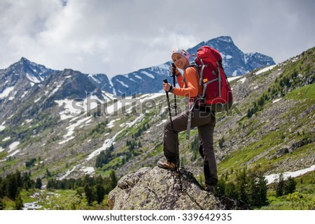 Young woman is hiking in highlands of Altai mountains, Russia