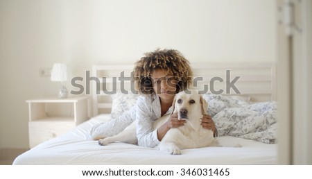 Young woman is holding a dog while laying on a bed in home - stock photo