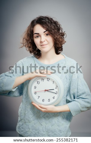 Young woman is holding big clock and pointing at it, isolated over gray background
