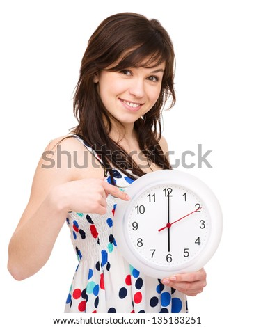 Young woman is holding big clock and pointing at it, isolated over white - stock photo