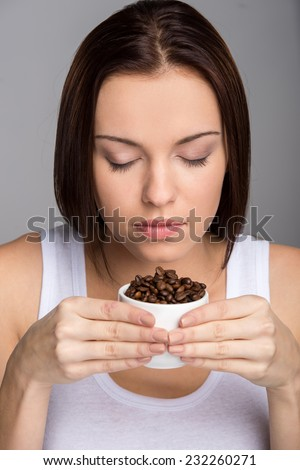 Young woman is holding coffee beans and sniffing.