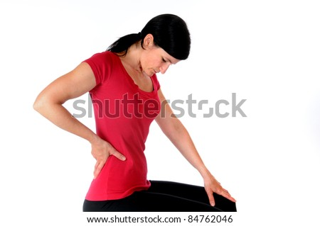 Young woman is holding her spine in front of a white studio background - stock photo