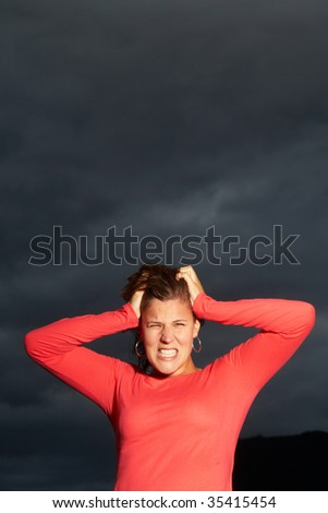 Young woman is in shock under a dark sky before a thunderstorm.