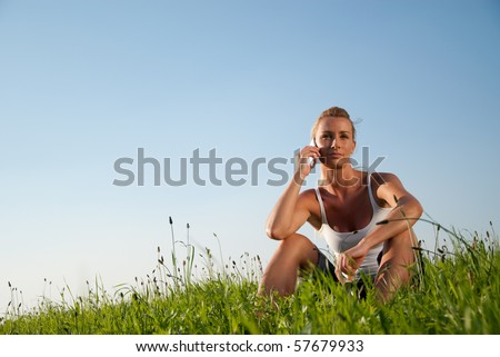 young woman is in the meadow and make phone calls - stock photo