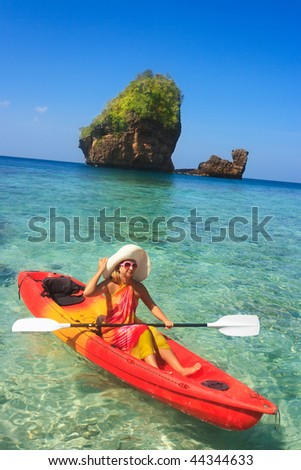 Young woman is kayaking in tropical lagoon