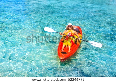 Young woman is Kayaking in tropical lagoon - stock photo