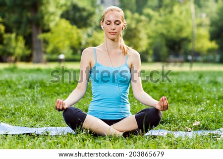 Young woman is listening music in the park and relaxing after exercise,Relaxation with music - stock photo