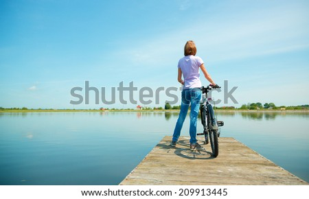 Young woman is looking at horizon standing on pier with bicycle, outdoor shoot - stock photo