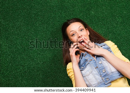 Young woman is lying on the grass and talking with someone on the phone,she is surprised because of something she hears.Surprised woman on the phone - stock photo
