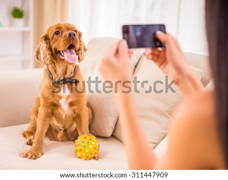 Young woman is making a picture with her cute dog pet. - stock photo