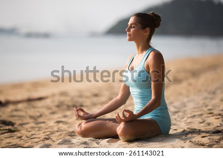 Young woman is making yoga on the beach - stock photo