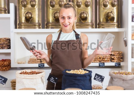 Young woman is offering nuts and on the plate is written Macadamia in Catalan in the store.