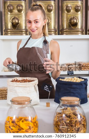Young woman is offering nuts and on the plate is written Pecana in Catalan in the store.