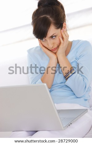 Young woman is on couch and working on laptop