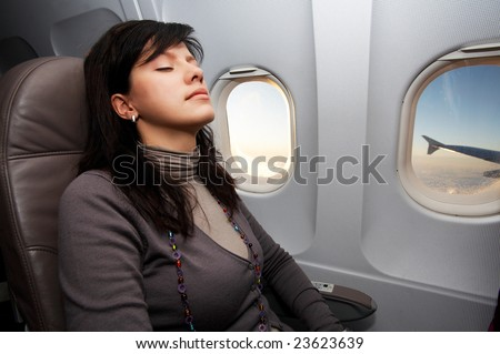 young woman is on passenger seat at airplane - stock photo