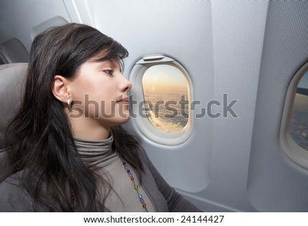 young woman is on passenger seat at airplane