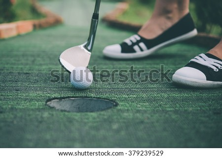 Young woman is playing mini golf. Toned picture - stock photo