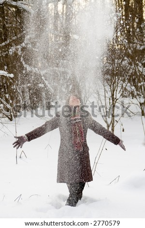 Young woman is playing with falling snow in the winter forest