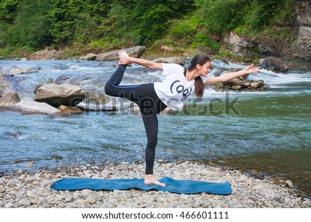 Young woman is practicing yoga at mountain river; 