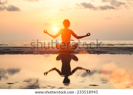 Young woman is practicing yoga at Sea beach. Silhouette with reflection in water. - stock photo