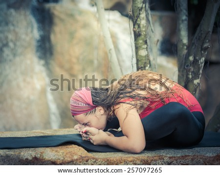 Young woman is practicing yoga near waterfall - stock photo