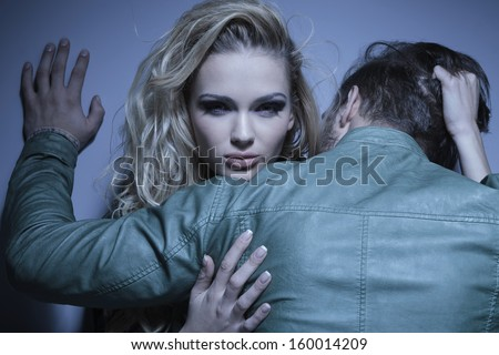 young woman is pulling her boyfriend to her by his hair, man standing with his back at the camera while embracing his lover - stock photo
