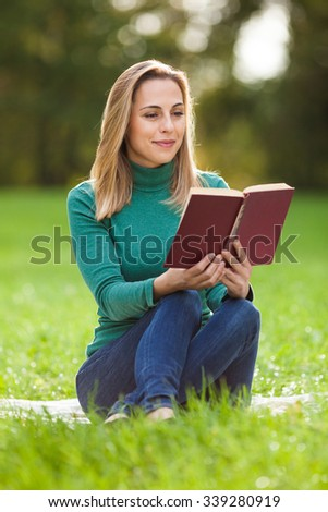 Young woman is reading a book in park