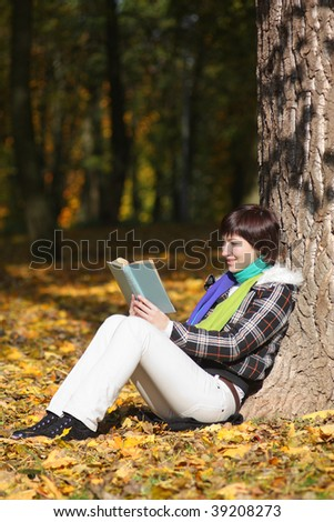 Young woman is reading book near the tree on a maple leafs - stock photo