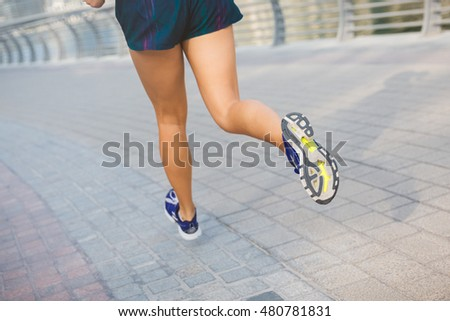 Young woman is running in sunny city. Morning jogging every morning.