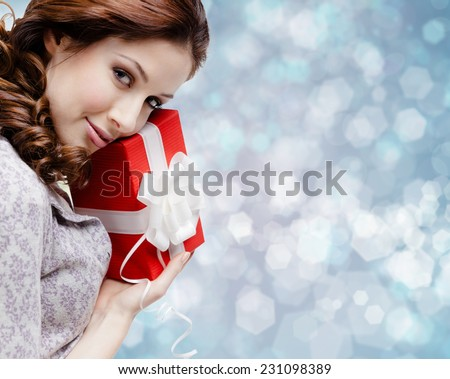Young woman is satisfied with a birthday gift wrapped in red paper, blue background - stock photo