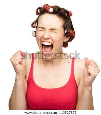 Young woman is screaming holding her fists tight while wearing hair-rollers, isolated over white - stock photo