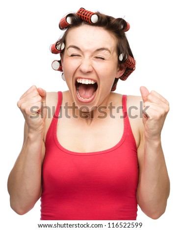 Young woman is screaming holding her fists tight while wearing hair-rollers, isolated over white