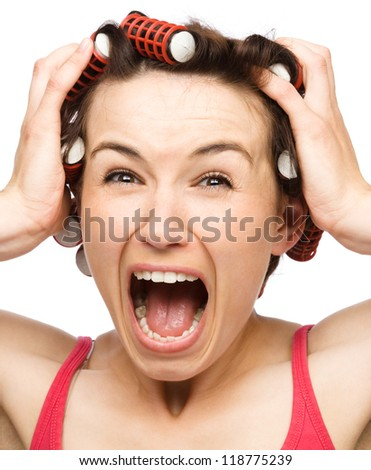 Young woman is screaming in terror holding her head with hands while wearing hair-rollers, isolated over white - stock photo