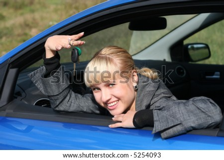 Young woman is siting in her car with key from it. She is smiling happy - stock photo