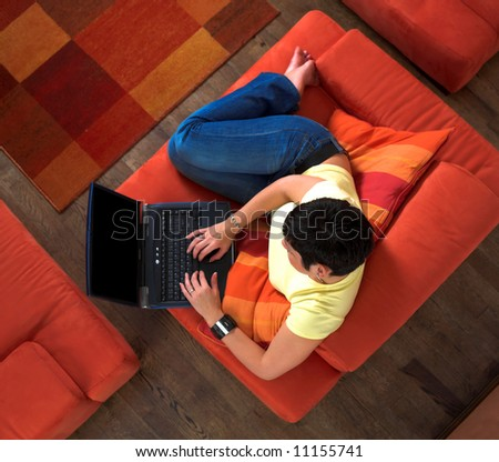 Young woman is sitting and resting on the sofa and using a laptop computer. Maybe she is surfing the net, chatting or studying for the next university exam. - stock photo