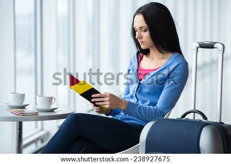 Young woman is sitting in the airport with coffee while waiting for flight. - stock photo