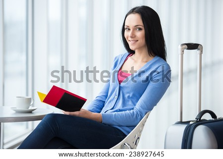 Young woman is sitting in the airport with coffee while waiting for flight. She is looking at the camera. - stock photo
