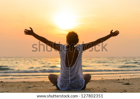 young woman is sitting on beach at sunrise - stock photo