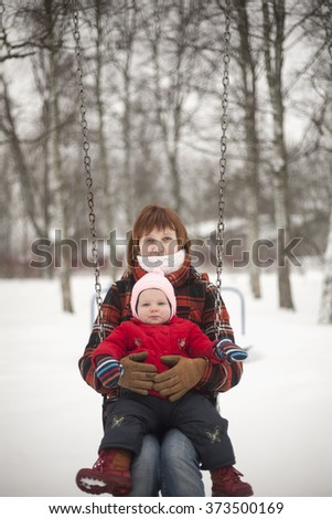 Young woman is sitting on swings in winter day, her little daughter is on her knees. - stock photo
