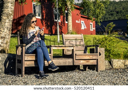 Young woman is sitting on the bench and searching something in t