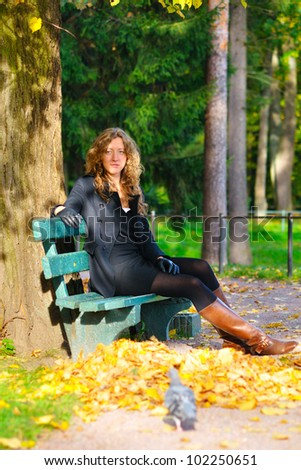 young woman is sitting on the bench in autumn park and looking at camera