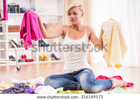 Young woman is sitting on the floor with clothes lying near her. - stock photo
