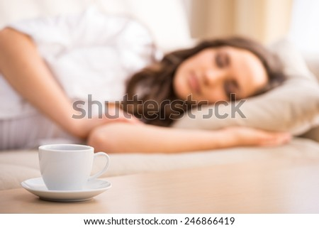 Young woman is sleeping in the bed. Focus on a cup on the table. - stock photo